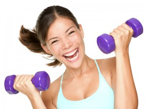 Happy fitness woman lifting dumbbells